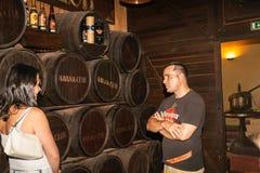 Guide in Havana Club famous rum distillery explans the process t. Havana, Cuba - June 30, 2012; Guide in front of barrels in Havana Club famous rum distillery stock image