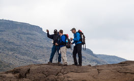 Guide instructs hiking tourists on mountain. Kilimanjaro, with its three volcanic cones, Kibo, Mawenzi, and Shira, is a dormant volcano in Kilimanjaro National Stock Photography