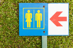 Guide post arrow to restroom for men and women on grass Royalty Free Stock Image