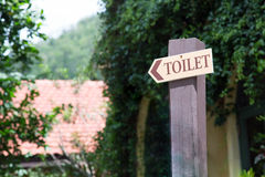 Guide post arrow to the toilet on wood column Royalty Free Stock Photos