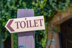 Guide post arrow to toilet on wood column Stock Photos