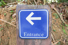 Guide post the entrance. Blue guide post the entrance is on the left Royalty Free Stock Photography