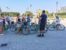 Guide prepares tourists for a bicycle tour in the middle of Paris, near the Louvre Museum. A guide talks with tourists before a bicycle tour of Paris. They are royalty free stock photography
