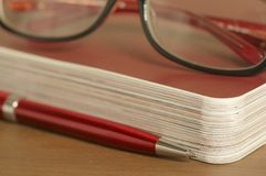 Guide, red ballpoint pen and glasses Stock Photography