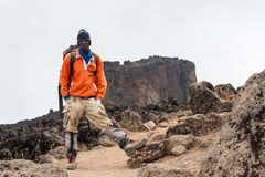 Guide stands before Lava Tower in Mt. Kilimanjaro. Kilimanjaro, with its three volcanic cones, Kibo, Mawenzi, and Shira, is a dormant volcano in Kilimanjaro Stock Photography
