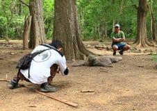Guide taking photos of tourist with komodo dragon Stock Photos