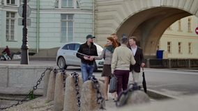 Guide tells something the tourist group on background of old building with arc. Guide tells something the tourist group on background of street full of cars stock footage