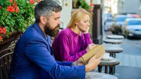 Guide to dating. Meeting people with similar interests. Man and woman sit cafe terrace. Girl interested what he reading. Guide to dating. Meeting people with stock image