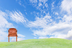 Guide wooden post on green field and sky Stock Photos