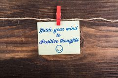 Guide your mind to positive thoughts. Write in sticky note with clothes pin and rope on wood Stock Image