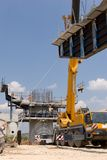 Guided frame. Crane lifting a metal frame to place it on pillar guided by a worker stock photography