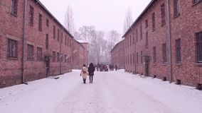 Guided tour to Auschwitz Birkenau, German Nazi concentration and extermination camp. Brick buildings in falling snow Stock Photo