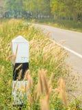 Guidepost около проселочной дороги с деревьями и лугами Стоковая Фотография