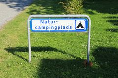 Guidepost, natur-campingplads at the countryside in Denmark in the summer. Sign guidepost, a natur campingplads in Denmark in the summer stock image