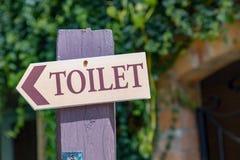 Guidi la freccia della posta alla toilette sulla colonna di legno Fotografie Stock
