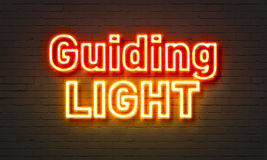 Guiding light neon sign on brick wall background. Stock Photo