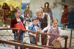 Guiding in museum. Mature teacher showing her pupils historical items in museum Royalty Free Stock Image