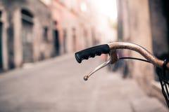 Guidon de bicyclette de ville, vélo au-dessus de beau backgr brouillé de bokeh Photographie stock libre de droits