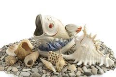 Guijarros, cáscaras y estatuilla de los pescados fotografía de archivo