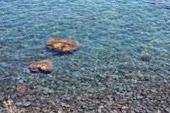 Guijarros de la playa bajo el agua clara Fotografía de archivo