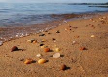 Guijarros de la playa en el borde del ` s del agua Fotografía de archivo