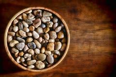 Guijarros de la roca del río en tazón de fuente de madera en el tablón de madera Imagen de archivo libre de regalías