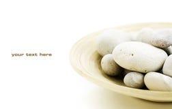 Guijarros en el tazón de fuente de bambú Fotos de archivo libres de regalías