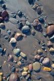 Guijarros mojados en la playa Fotos de archivo