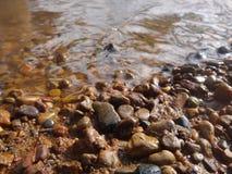 Guijarros mojados en la playa cerca del agua Fotos de archivo