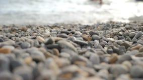 Guijarros que caen en la playa, guijarros coloreados multi de la playa metrajes