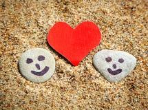 Guijarros y forma del corazón en la arena Imágenes de archivo libres de regalías