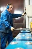 A guilhotina de funcionamento do trabalhador corta a máquina Imagens de Stock Royalty Free