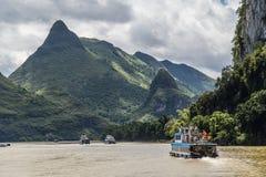 Guilin, China - circa July 2015: Cruise boat sails between karst mountains and limestone peaks of Li river in   China Royalty Free Stock Image