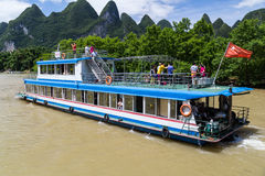 Guilin, China - circa July 2015: Cruise boat sails between karst mountains and limestone peaks of Li river in   China Royalty Free Stock Photography
