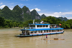 Guilin, China - circa July 2015: Cruise boat sails between karst mountains and limestone peaks of Li river in   China Stock Photography