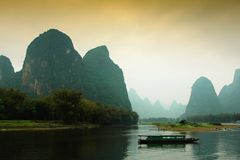 Guilin china landscape. A fishing boat along water of Guilin China, surrounded by what is frequently called 'grotesque' mountains royalty free stock photo