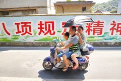Three person family rides a scooter with umbrella protecting from the sun. Guilin, China - September 16, 2017: Three person family rides a scooter with umbrella Royalty Free Stock Images