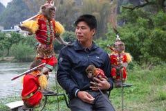 GUILIN KINA - 6 APRIL 2011, man som arbetar med apor i dräkt royaltyfria bilder