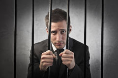 Guilty businessman. Sad young businessman behind bars Royalty Free Stock Photo