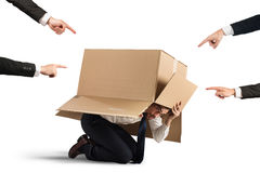 Guilty. Businessman indicated by colleagues hiding in a cardboard Royalty Free Stock Photos