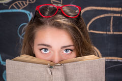 Guilty eyes of young student girl hiding behind a book. Perplexed  young student girl in red dress and red glasses reading a book hides behind it Stock Images