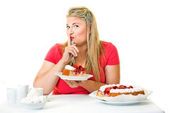 Guilty fat woman eating a slice of cream cake. Putting her finger to her lips in a hushing gesture asking the viewer to keep her secret Royalty Free Stock Photography