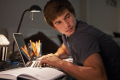 Guilty Looking Teenage Boy Studying At Desk In Bedroom In Evening On Laptop Royalty Free Stock Photography