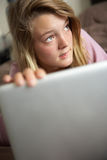 Guilty Looking Teenage Girl Using Laptop At Home Stock Photos