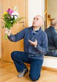 Guilty man asks forgiveness. Guilty man kneeling with bouquet of flowers stock photography