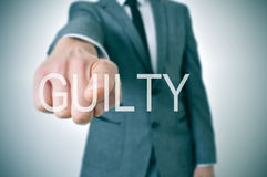 Guilty. Man wearing a suit pointing the finger to the word guilty written in the foreground stock photography