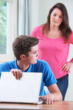 Guilty Teenage Boy Hiding Internet Browsing From Mother. Guilty Teenage Boy Hides Internet Browsing From Mother Stock Photo