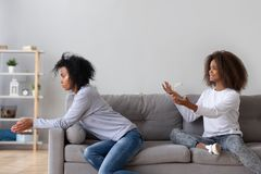 Guilty teenage daughter ask forgiveness from young mom. Desperate crying African American teenage daughter sit on couch asking forgiveness from young mom, guilty royalty free stock photos