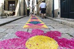 Guimaraes, Braga, Portogallo 14 agosto 2017: Il vicolo stretto del ciottolo con gli ornamenti molto variopinti si è formato dalle Fotografie Stock Libere da Diritti