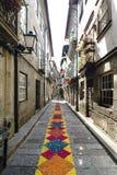 Guimaraes, Braga, Portogallo 14 agosto 2017: Il vicolo stretto del ciottolo con gli ornamenti molto variopinti si è formato dalle Immagine Stock